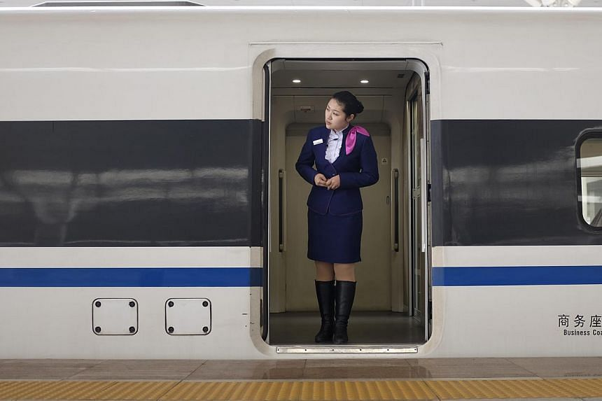 A train employee looks out from an entrance of a CRH (China Railway High-speed) Harmony bullet train at Zhengzhou East Railway Station in Zhengzhou, Henan province on Feb 17, 2014. China Railway Construction Corp has signed a US$13.1 billion (S$16.3