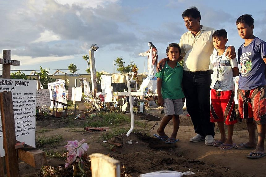 Mr Pete Lacandazo, 58, with his grandsons Jerald (in green), 8, John Paul (second from right), 12, and adopted grandson Rex (right), 13, at the mass grave of their 22 perished family members in San Joaquin church in Palo, Leyte province, in central P