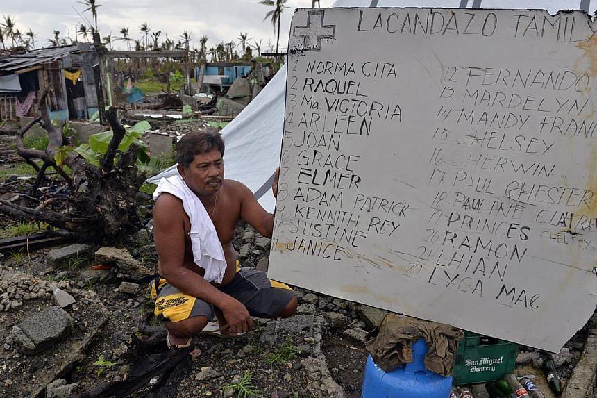 Mr Pete Lacandazo, with a sign in his backyard which lists the names of all 22 family members who perished when their home was hit by Super Typhoon Haiyan on Nov 8 2013. -- ST FILE PHOTO: DESMOND FOO