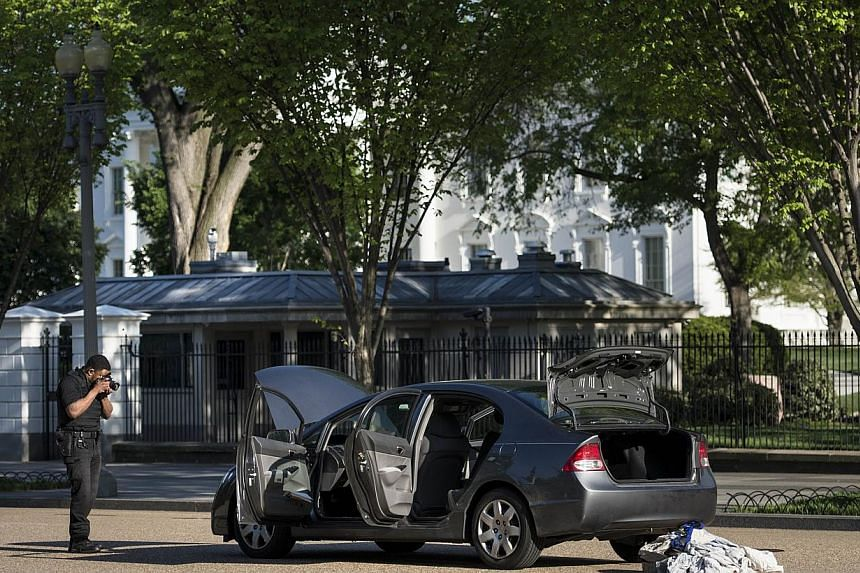 A member of the Secret Service photographs a car near the White House on Pennsylvania Avenue on May 6, 2014 in Washington, DC. A car trailed an official motorcade that was carrying the daughters of US President Barack Obama on Tuesday, sparking