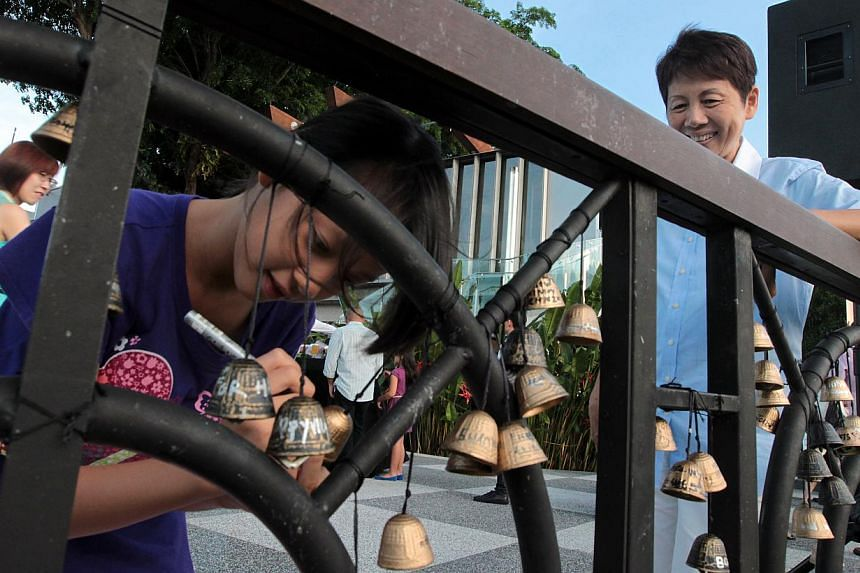 A young visitor (above) writing a wish on a bell as her grandmother looks on. Mount Faber, Singapore's second oldest park, has unveiled a casual and more accessible concept. A bartender (below) from Spuds & Aprons diner performing during the receptio
