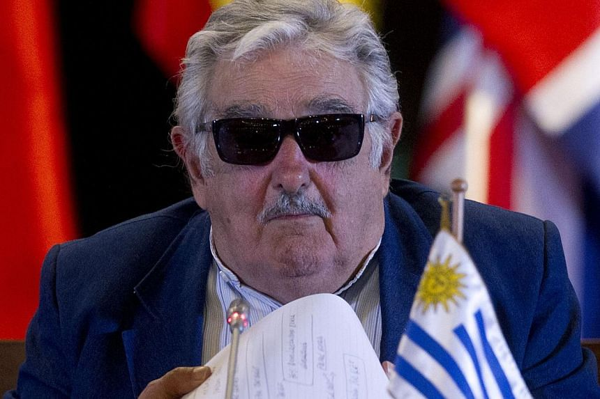 Uruguayan President Jose Mujica gestures during a meeting of the Economic Commission for Latin America and the Caribbean (Cepal) in Santiago, on March 12, 2014. Mr Mujica on Tuesday signed off on regulations for his country's landmark legalisation of