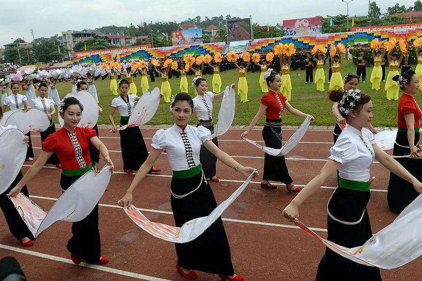 Dancers perform during official celebrations of the 60th anniversary of Vietnam's Dien Bien Phu victory over France at a stadium in the Northwestern town of Dien Bien Phu on May 7, 2014. War veterans, communist leaders and diplomatas gathered in Viet