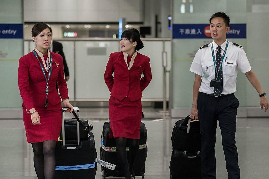 Flight attendants (left and centre) for Cathay Pacific are seen arriving at the international airport in Hong Kong on May 5, 2014. -- PHOTO: AFP
