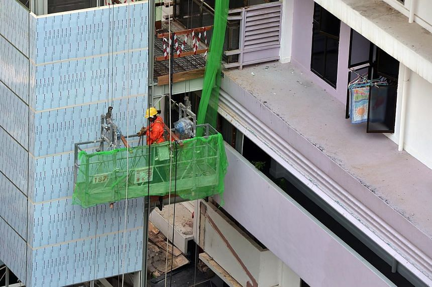 A construction worker is seen at the Lift Upgrading Programme (LUP) in the Henderson Crescent estate. The Manpower Ministry and Building and Construction Authority will lead a new workgroup to work out details of a mandatory framework that will incor