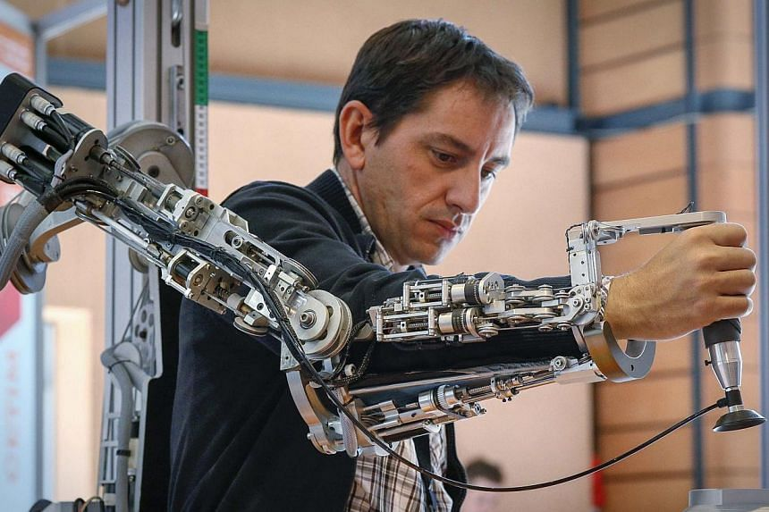A visitor tests an exoskeleton from CEA during the Innorobo 2014 fair (Innovation Robotics Summit) in Lyon March 18, 2014. -- PHOTO: REUTERS