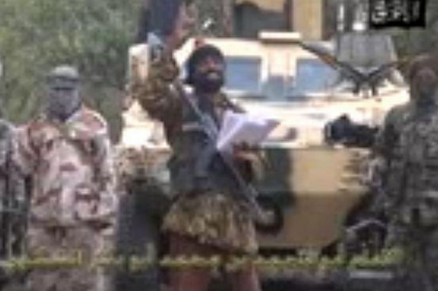 A grab made on May 5, 2014, from a video obtained by AFP shows the leader of the Islamist extremist group Boko Haram Abubakar Shekau (centre) delivering a speech. -- FILE PHOTO: AFP