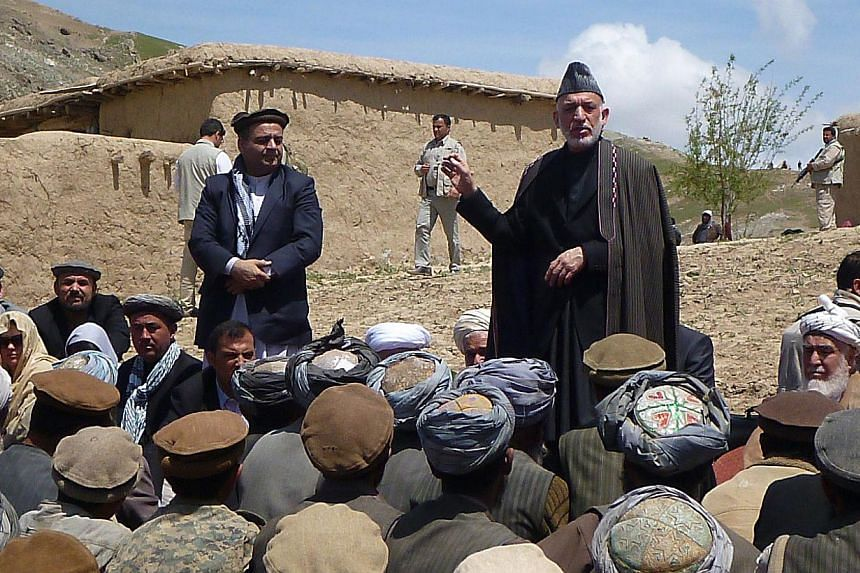 Afghan President Hamid Karzai (right) talks with displaced villagers during a visit to the site of a deadly landslide in Aab Bareek village in the Argo district of Badakhshan on May 7, 2014. Mr Karzai visited a refugee camp for victims of a deadly la