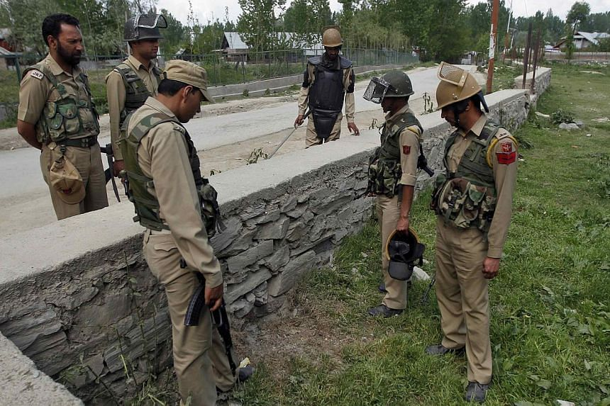 Indian police inspect the site of a bomb explosion outside a polling station at Palhalan in Baramulla district, north of Srinagar on May 7, 2014. A bomb blast near a polling booth in Kashmir injured a policeman on Wednesday, amid further stone-throwi