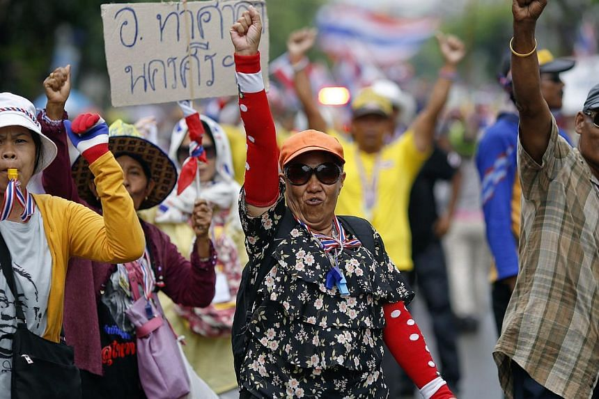 Anti-government protesters marching in the city centre celebrate shortly after a Thai court delivered its verdict on Prime Minister Yingluck Shinawatra in Bangkok on May 7, 2014. The Thai court found Yingluck guilty on Wednesday of violating the cons
