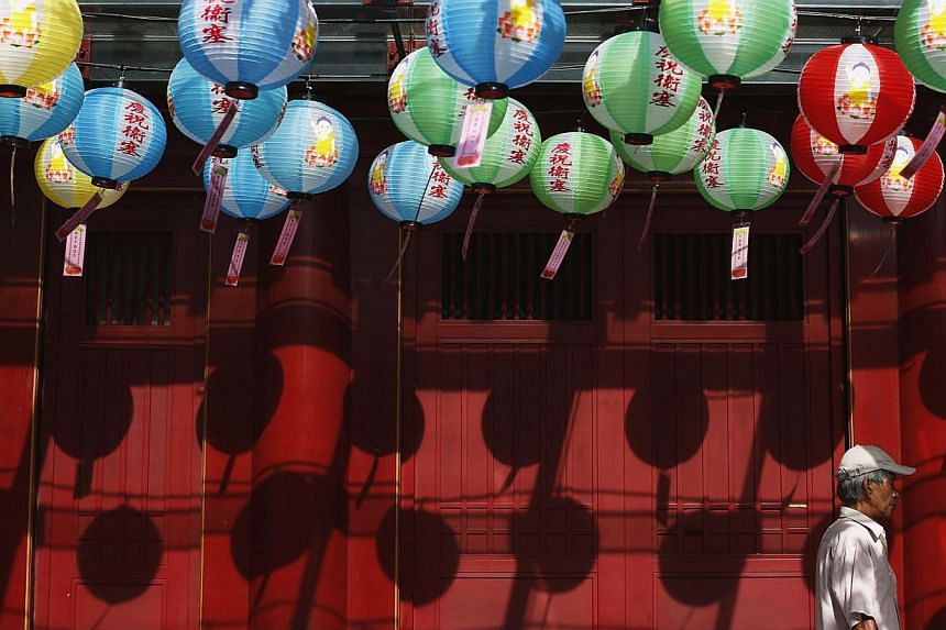 A man passes lanterns carrying well-wishes from devotees outside the Buddha Tooth Relic Temple ahead of Vesak Day in Singapore on May 6, 2014. Animals should not be released as part of Vesak Day celebrations, the National Parks Board (NParks) wa