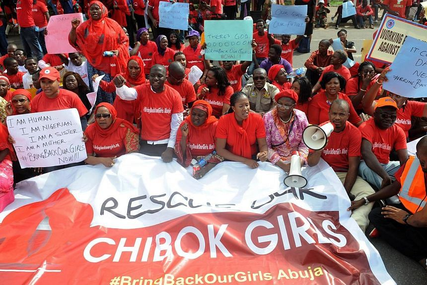 Members of civil society groups sit to protest the abduction of Chibok school girls in Abuja on May 6, 2014, ahead of World Economic Forum. Britain will send a small team of experts to Nigeria to help respond to the kidnap of more than 200 girls, a s