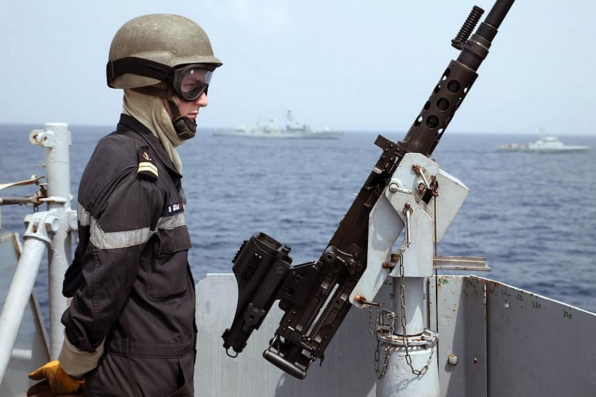 A sailor aboard the French Navy ship Commandant Birot waits to take part in a training exercise in the Gulf of Guinea, off Tema harbour near Accra on Feb 20, 2014. The cost of Somali piracy to the global economy fell by almost half last year as attac