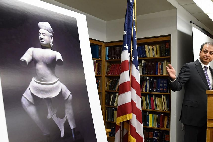 Preet Bharara, US Attorney for the Southern District of New York, speaks at a ceremony held to commemorate the return of the Duryodhana (left, in photograph), a 10th Century sandstone sculpture, to Cambodia on May 7, 2014 at the US Attorney's office