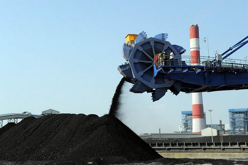 In this photograph taken on Feb 18, 2011, Indian workers use heavy machinery to sift through coal at the Adani Power company thermal power plant at Mundra some 400kms from Ahmedabad. -- PHOTO: AFP