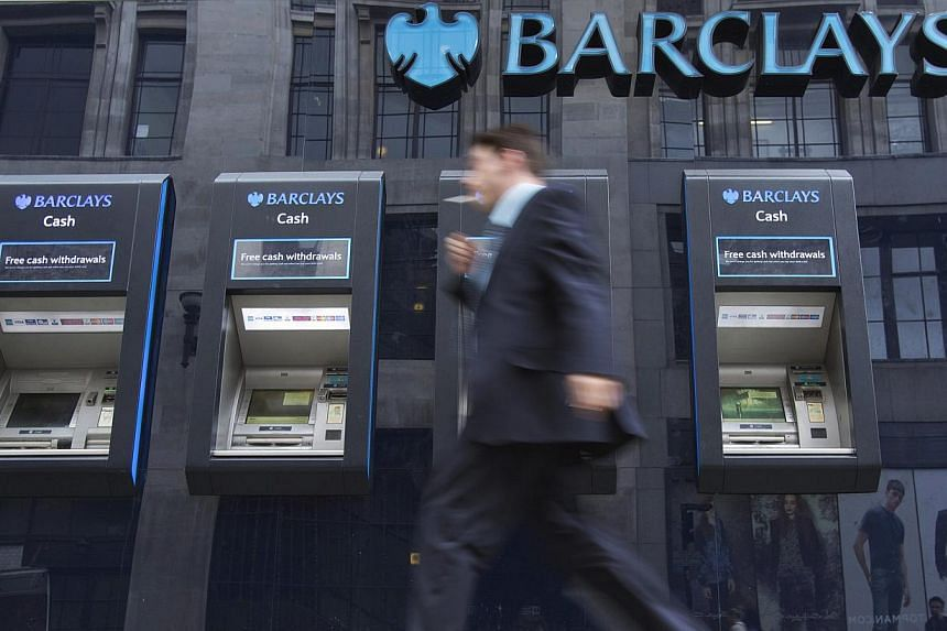 A man passes automated teller machines at a Barclays bank branch in London, on Aug 30, 2012. -- FILE PHOTO: REUTERS