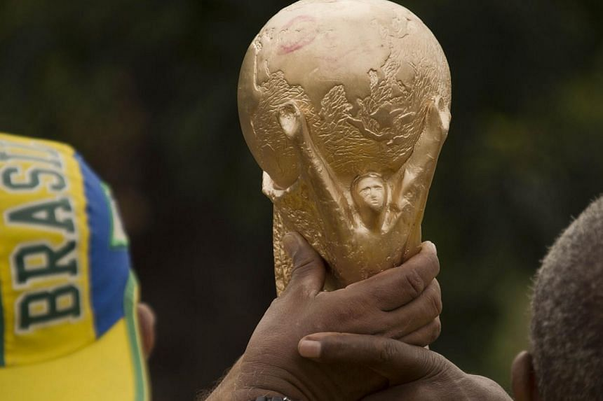 Brazilian fans hold a fake world cup as the coach of the Brazilian national football team, Luiz Felipe Scolari, announces his 23-men squad for the upcoming Fifa World Cup Brazil 2014, during a presss conference in Rio de Janeiro, Brazil on May 7, 201
