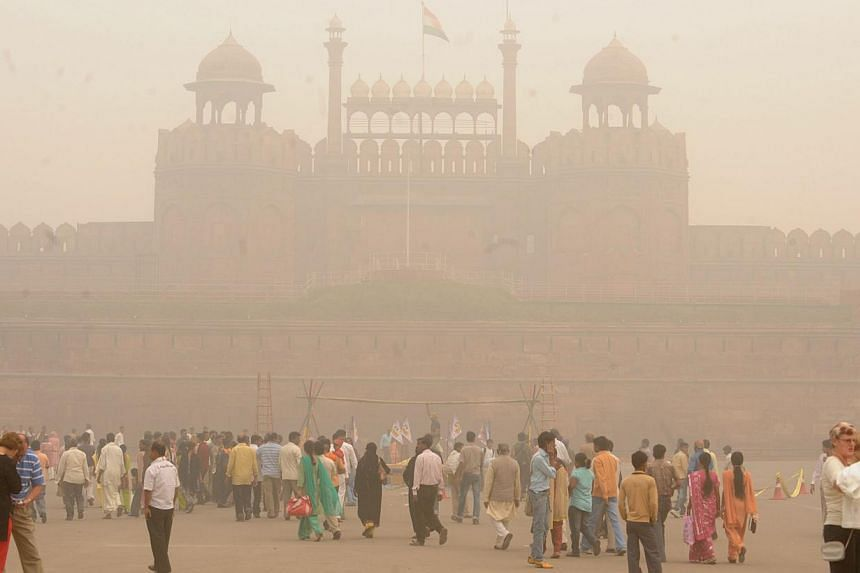 Pedestrians and visitors gather as smog envelopes The Red Fort in New Delhi on Nov 7, 2009. -- FILE PHOTO: AFP