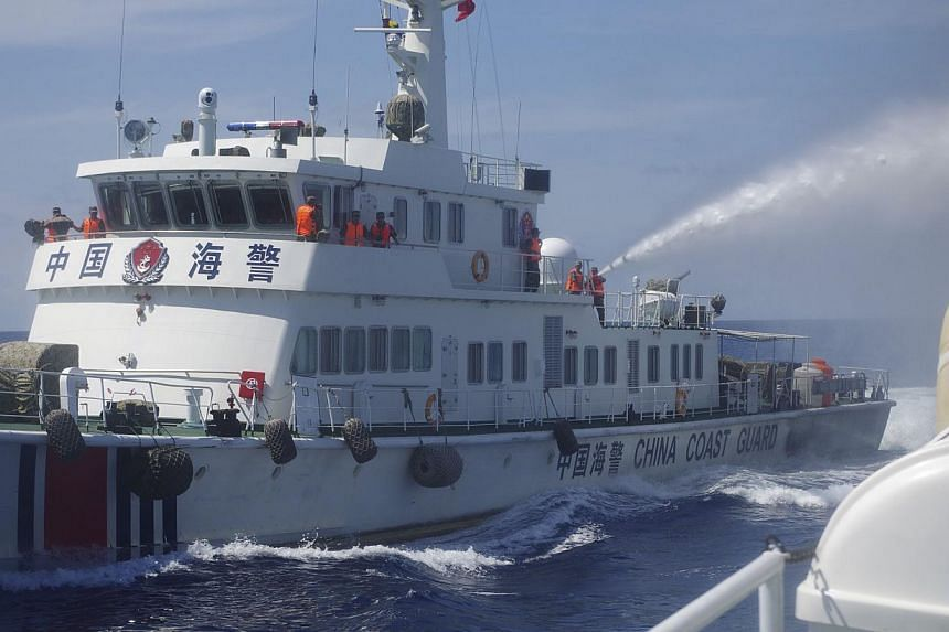 A Chinese ship (L) uses water cannon on a Vietnamese Sea Guard ship on the South China Sea near the Paracels islands, in this handout photo taken on May 2, 2014 and released by the Vietnamese Marine Guard on May 8, 2014.