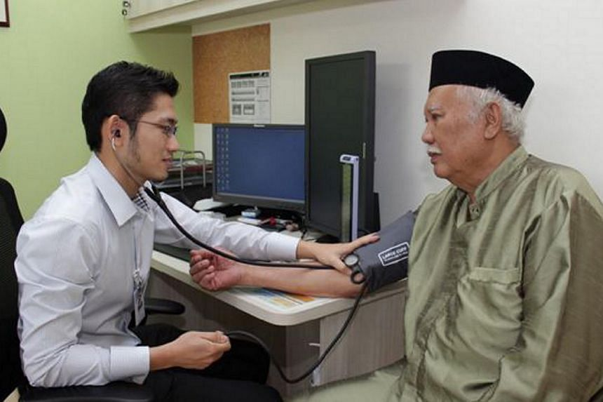Mr Kamari Hassan (right), a retired mechanic, going through a medical check-up with his family doctor, Dr Gilbert Yeo, at the Family Medicine Clinic (FMC) Ang Mo Kio. Singapore's fifth FMC opened officially at Chinatown Point on Thursday, adding to e