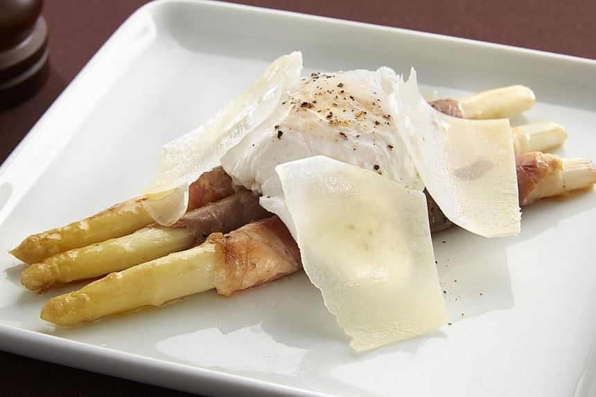 Prosciutto-wrapped sauteed white asparagus with poached egg and parmesan cheese from Arossa Wine & Grill Bar. -- PHOTO:PUBLICIST PR