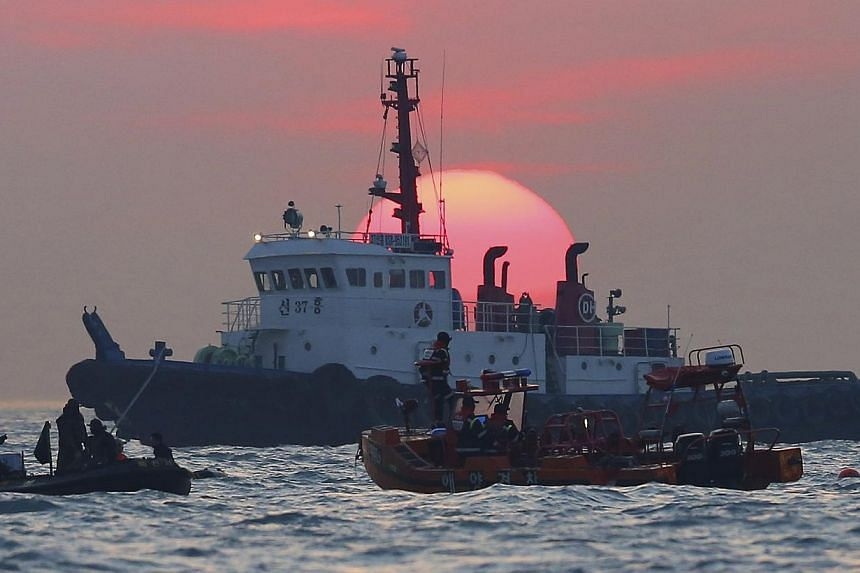 South Korean rescue workers operate during sunset near the site where the capsized ferry Sewol sank, during a search and rescue operation in the sea off Jindo on April 24, 2014. The head of the maritime company that owns the South Korean ferry t