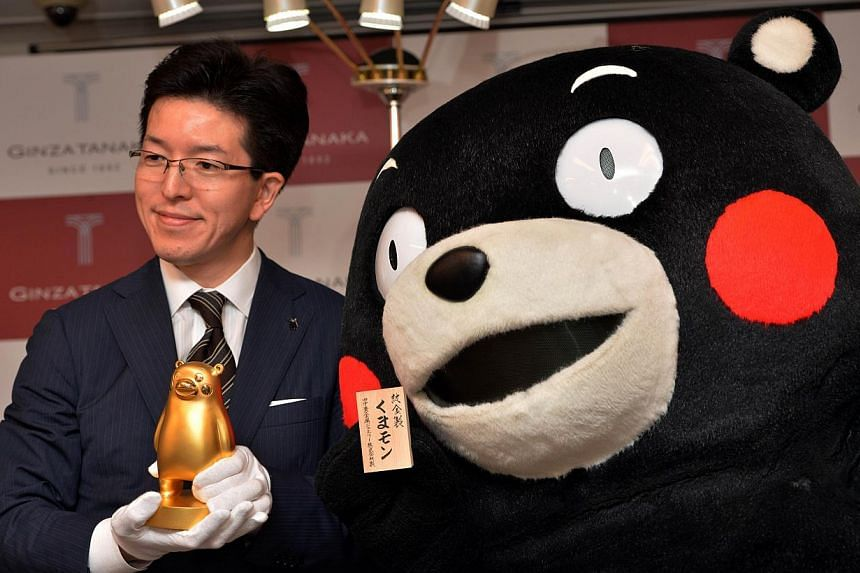 Japan's jeweller Tanaka Kikinzoku Jewelry president Masakazu Tanaka displays a pure gold Kumamon figure in Tokyo on May 1, 2014. -- FILE PHOTO: AFP