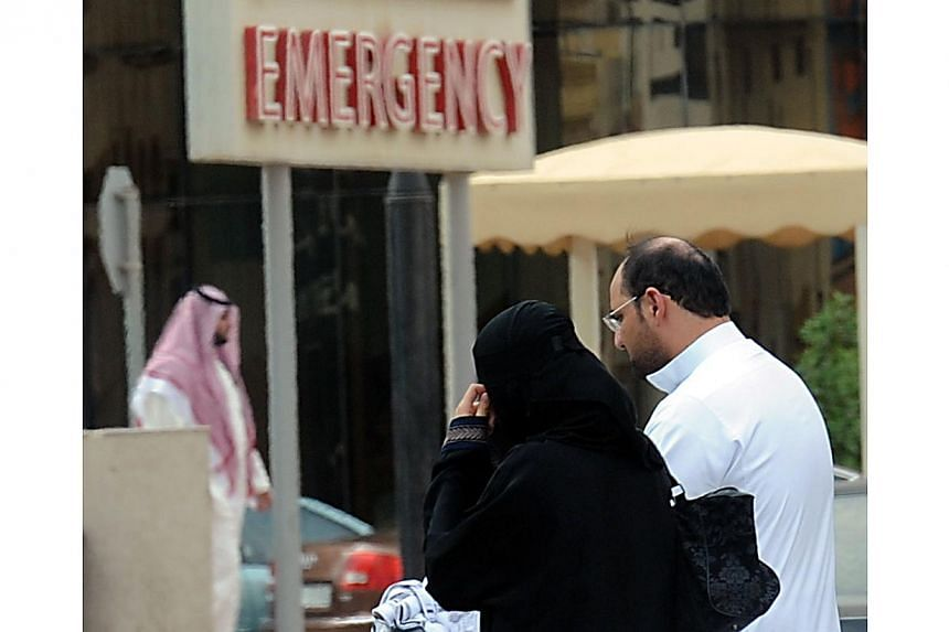 A Saudi couple walk past a board showing the way to a local hospital's emergency department in the Saudi capital Riyadh on April 27, 2014. Saudi Arabia has announced four more deaths from the Mers coronavirus and 18 new infections, as it battles to c