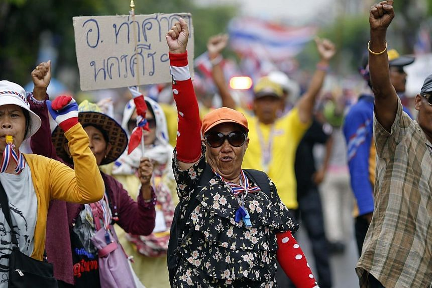 Anti-government protesters marching in the city centre celebrate shortly after a Thai court delivered its verdict on Prime Minister Yingluck Shinawatra, in Bangkok on May 7, 2014. Thai protesters who have massed on Bangkok's streets for six months sa