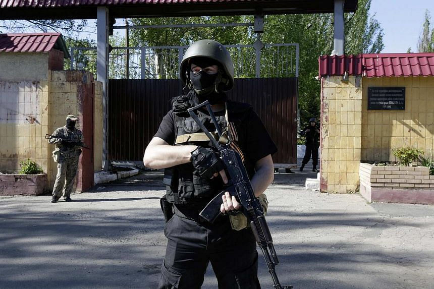 Pro-Russian armed separatists guard a street near an administrative building in Donetsk on May 6, 2014. Pro-Moscow rebels fighting in east Ukraine vowed on Thursday to press on with a disputed independence referendum, ignoring a call from President V