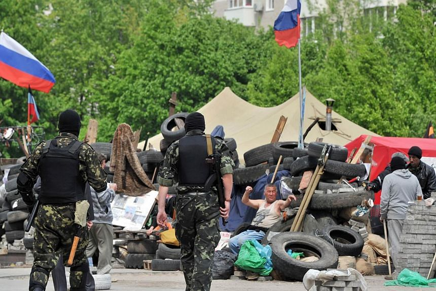 Pro-Russian militants walk at a barricade outside the seized regional state building in the eastern Ukrainian city of Donetsk on May 5, 2014. An independence vote in east Ukraine will go ahead this weekend as planned, rebels there said Thursday, desp