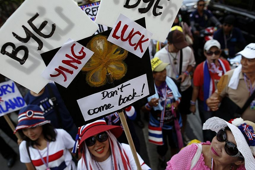 Anti-government protesters carry signs against ousted Prime Minister Yingluck Shinawatra as they march in central Bangkok on May 8, 2014. Thailand's National Anti-Corruption Commission found former Prime Minister Yingluck Shinwatra guilty of negligen