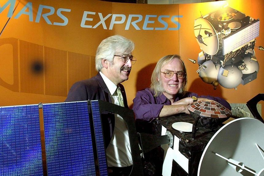 Professor Colin Pillinger (right) from the open university and project leader of the Beagle 2 satellite to Mars programme posing with professor David Southwood (left) from the European Space Agency behind a model of the Beagle 2 satellite in London o