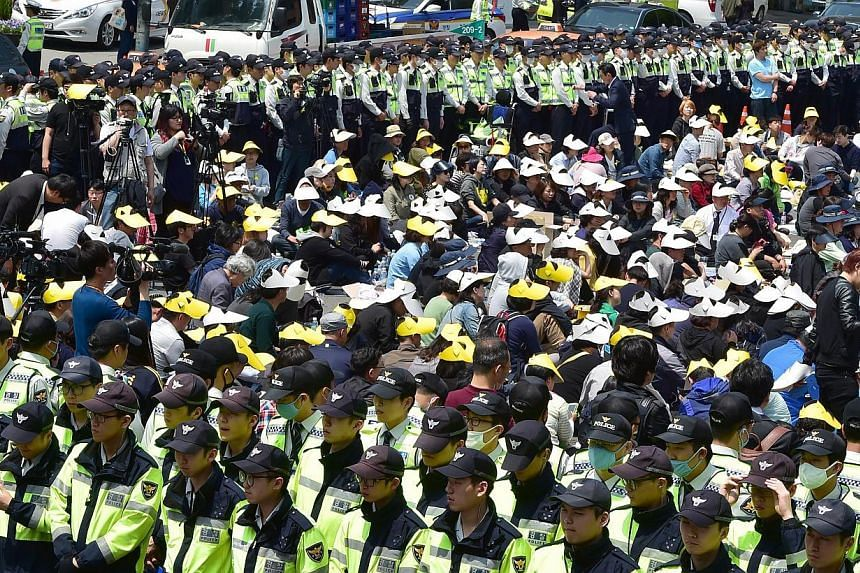 Policemen surround relatives of victims of the sunken South Korean ferry Sewol as they stage a sit-in protest on a street near the presidential Blue House in Seoul on May 9, 2014. -- PHOTO: AFP