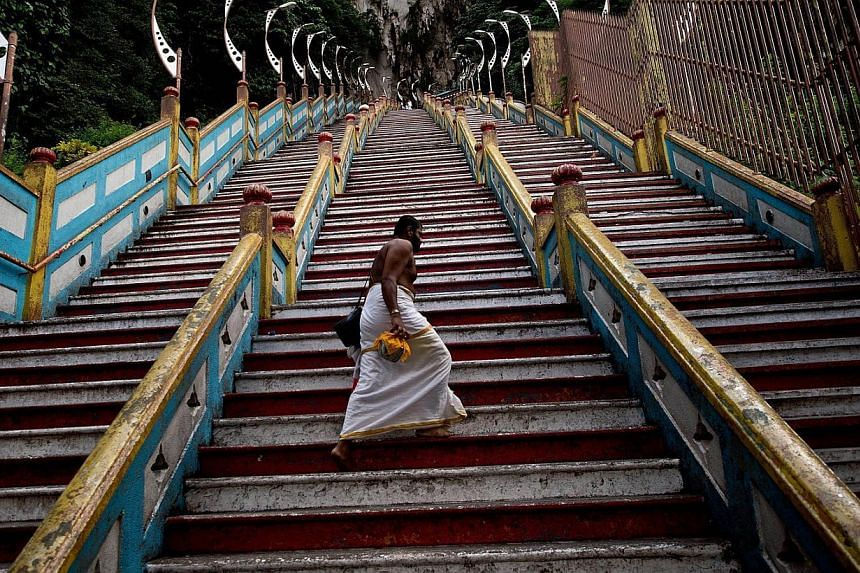 A Hindu priest walks up the 272 stairs to the Batu Caves temple outside of Kuala Lumpur on May 9, 2014. -- PHOTO: AFP