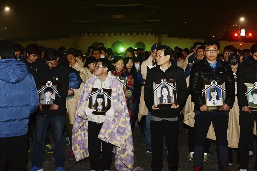 Parents holding portraits of their children, who died on sunken passenger ship Sewol, march towards the Presidential Blue House in central Seoul on May 9, 2014. -- PHOTO: REUTERS