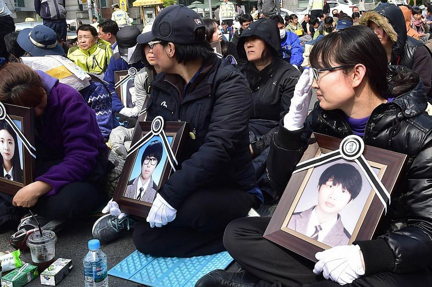 Relatives holding portraits of their children who perished when the Sewol ferry sank with the loss of around 300 lives stage a sit-in protest demanding to see South Korean President Park Geun Hye on a street near the presidential Blue House in Seoul