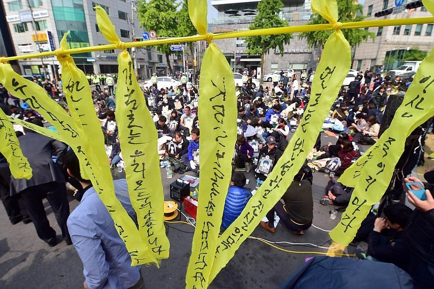 Yellow ribbons hang on a wire as relatives holding portraits of their children who perished when the Sewol ferry sank with the loss of around 300 lives stage a sit-in protest demanding to see South Korean President Park Geun Hye on a street near the