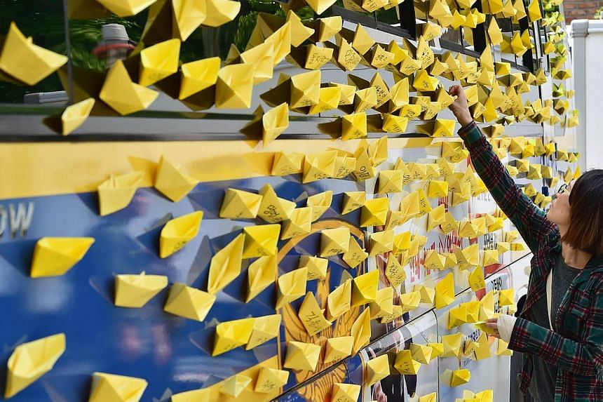 A protestor puts up yellow origami boats on the side of a police vehicle while relatives with children who perished when the Sewol ferry sank with the loss of around 300 lives staged a sit-in protest demanding to see South Korean President Park Geun