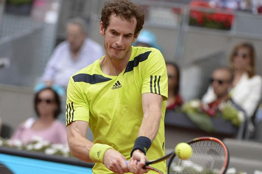 British player Andy Murray returns the ball to Colombian player Santiago Giraldo during their men's singles third round tennis match of the Madrid Masters at the Magic Box (Caja Magica) sports complex in Madrid on May 8, 2014. -- PHOTO: AFP