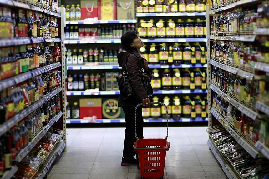 A customer looks at items displayed on shelves at a supermarket in Shenyang, Liaoning province on April 11, 2014. China's annual inflation fell sharply to 1.8 per cent in April, the lowest in 18 months, official data showed Friday, raising concerns a