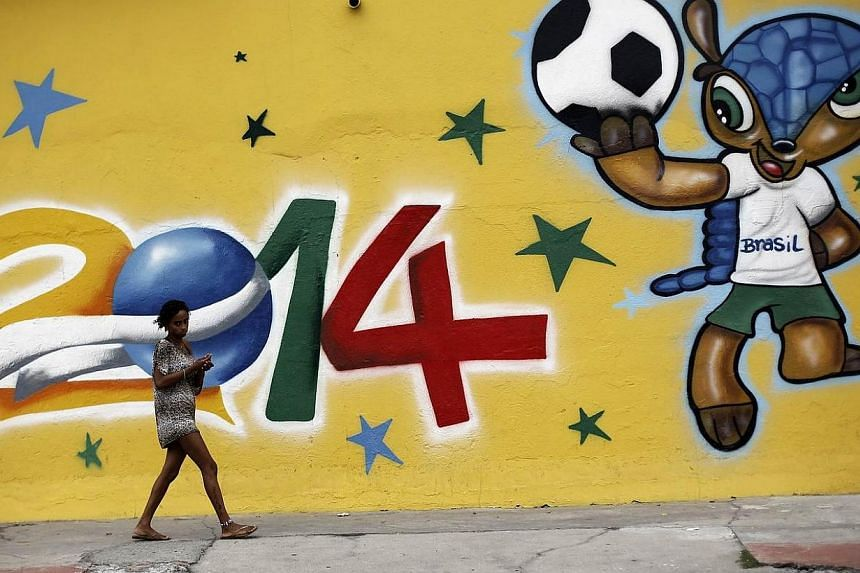 A woman walks past a graffiti painted with the official mascot of the 2014 World Cup, Fuleco the Armadillo, in Sao Paulo on May 7, 2014.Winners of the World Cup contest held by The Straits Times in partnership with Komoco Motors will have a vet