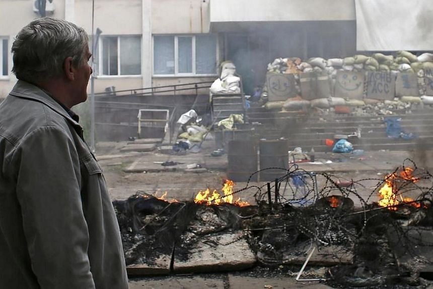 A man looks at the burned police headquarters in the southeastern port city of Mariupol on May 9, 2014. Three people were killed and 25 wounded on Friday, May 9, 2014, in fighting between the Ukrainian military and pro-Russian supporters in the
