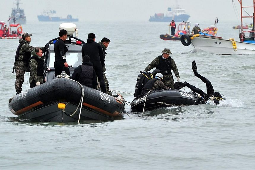 A South Korean Navy's SSU member (right) dives to rescue missing passengers of a capsized ferry at sea off Jindo on April 19, 2014. -- FILE PHOTO: AFP
