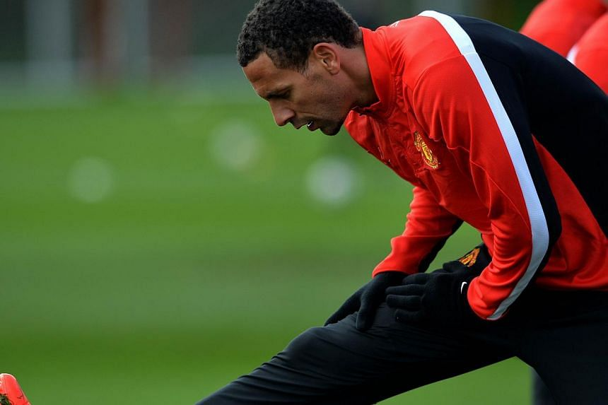 Manchester United's English defender Rio Ferdinand does stretching exercises during a team training session at their Carrington training complex in Manchester, north-west England, on April 8, 2014, on the eve of their Uefa Champions League second leg