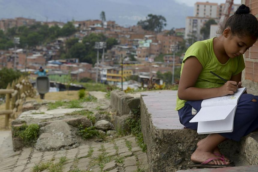 A woman (left) using Medellin's Metrocable system and a girl (right) studying outside her home in Moravia shanty town last month, when the World Urban Forum was held in the Colombian city. Once notorious for its drug gangs, Medellin has made major ef