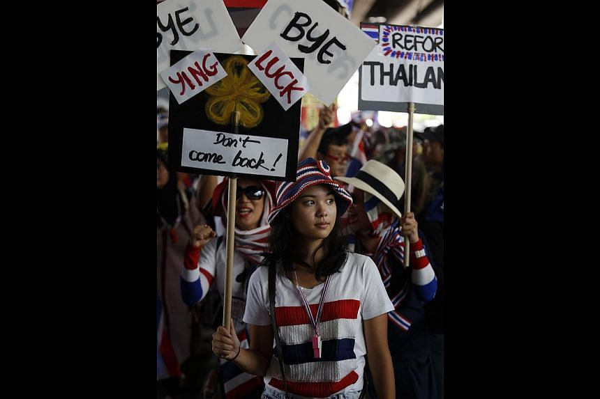 Anti-government protesters marching in Bangkok yesterday. The anti-corruption commission is looking into the possibility of filing criminal charges against Ms Yingluck, which could result in her facing jail time.