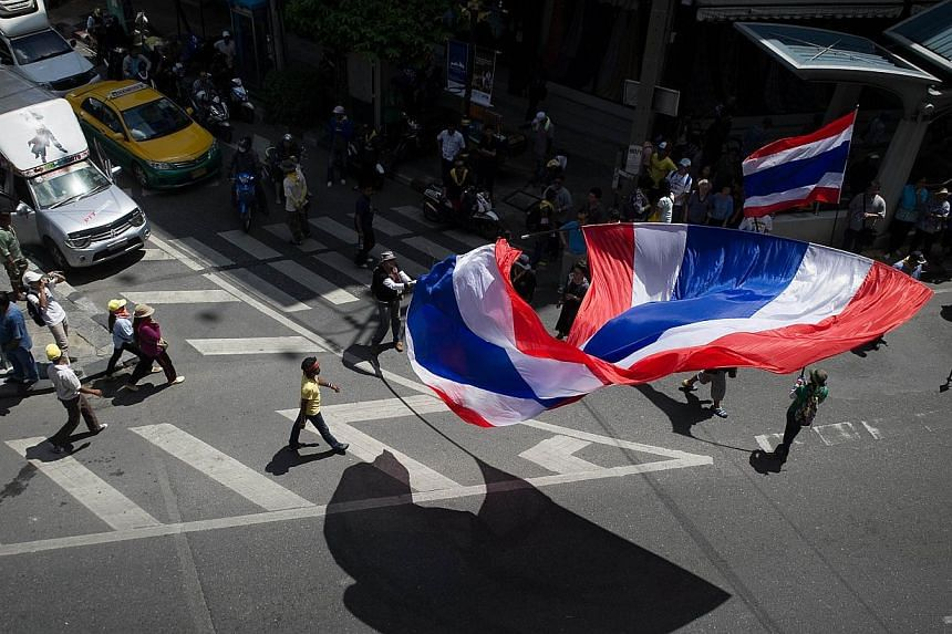 "People carry Thai flags as anti-government protesters march along a street in Bangkok on May 8, 2014. Thai protesters vowed on Friday to besiege television stations and police positions as they launched a ""final fight"" to topple a government that is"