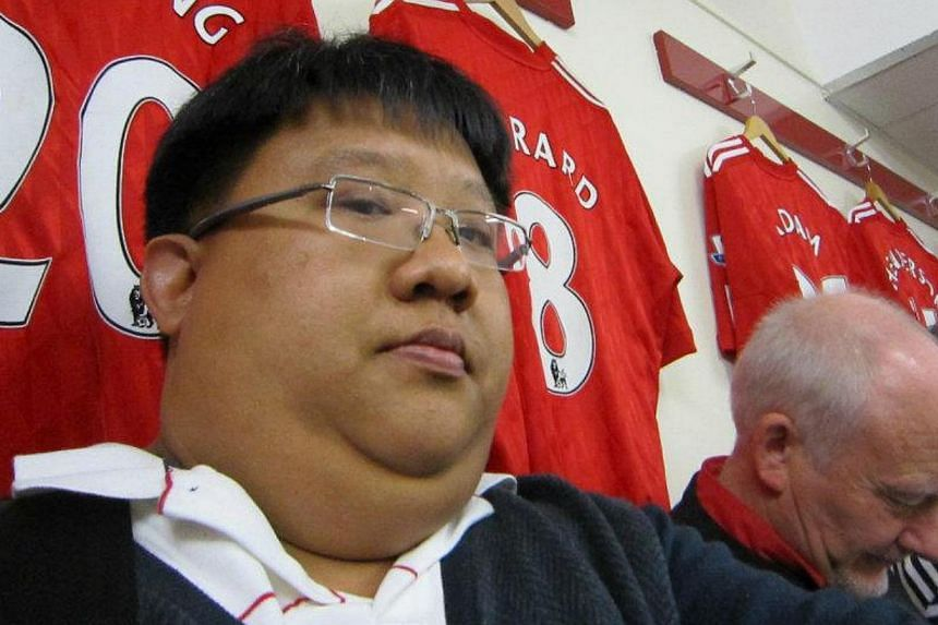 The writer posing beside Steven Gerrard's jersey inside the Anfield dressing room during his previous trip in 2012.-- ST PHOTO: CHIA HAN KEONG