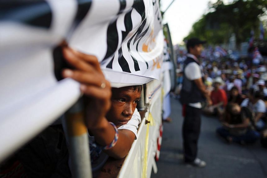 A boy peers from inside a truck used as a stage for anti-government protesters outside the parliament building in Bangkok on May 9, 2014. Thai police fired teargas on Friday at royalist protesters bent on bringing down a caretaker government after a
